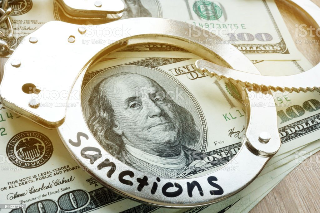 Word sanctions on a handcuffs and dollars. Economical restrictive measures. stock photo