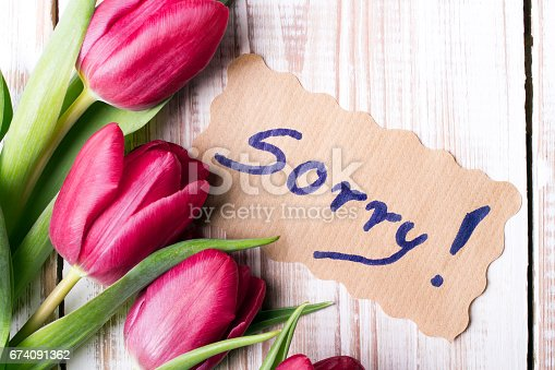istock word SORRY and bouquet of tulips on wooden background 674091362