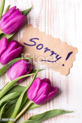 istock word SORRY and bouquet of tulips on wooden background 685876626