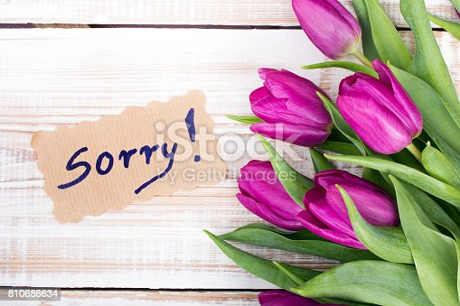 istock word SORRY and bouquet of tulips on wooden background 810686634