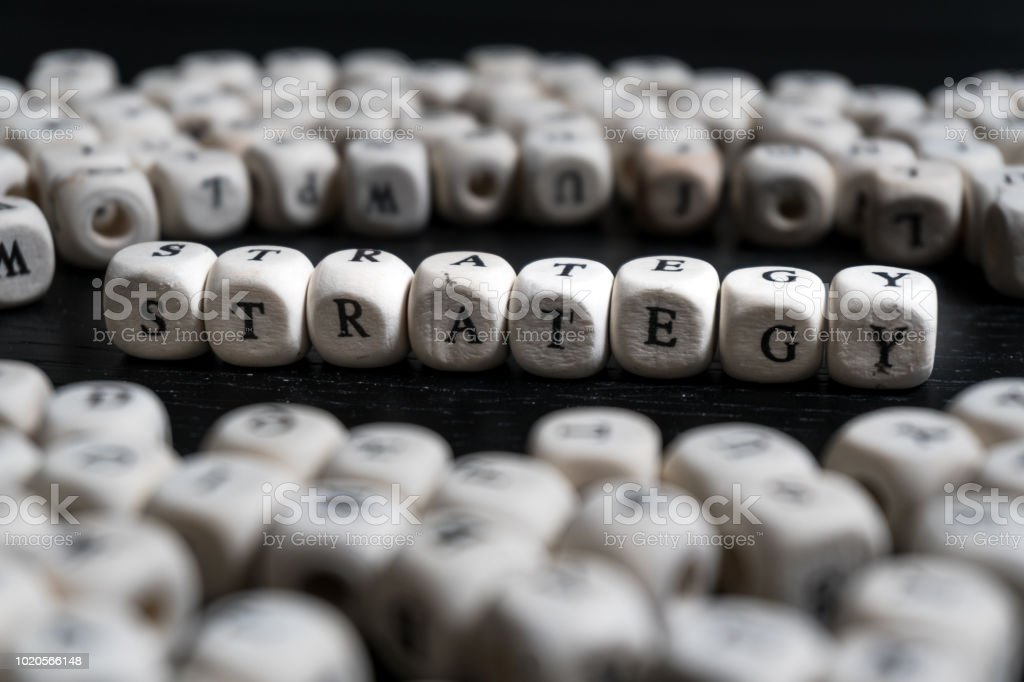 Word STRATEGY on wooden cubes on a black wooden table with copy space stock photo
