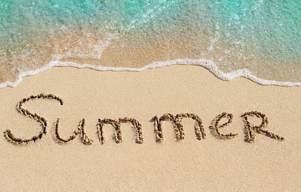 Word Summer handwritten on sand stock photo
