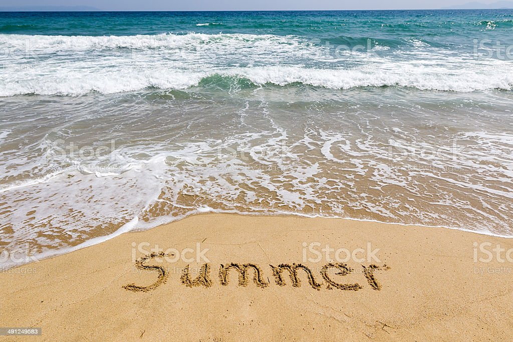 Word summer written in sand on the beach stock photo