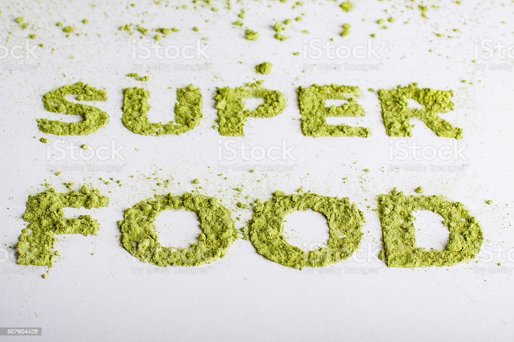 Word superfood piled of green powder of barley grass. stock photo