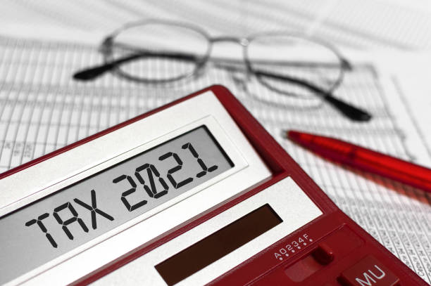 Word Tax 2021 on calculator. Glasses, pen and the calculator on documents. The concept of financial stability,Income Statement Word Tax 2021 on calculator. Glasses, pen and the calculator on documents. The concept of financial stability,Income Statement taxes stock pictures, royalty-free photos & images