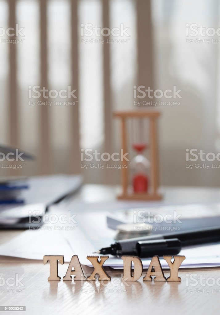 Word TAX DAY composed of wooden letters. Coins, papers, pen in the background. stock photo