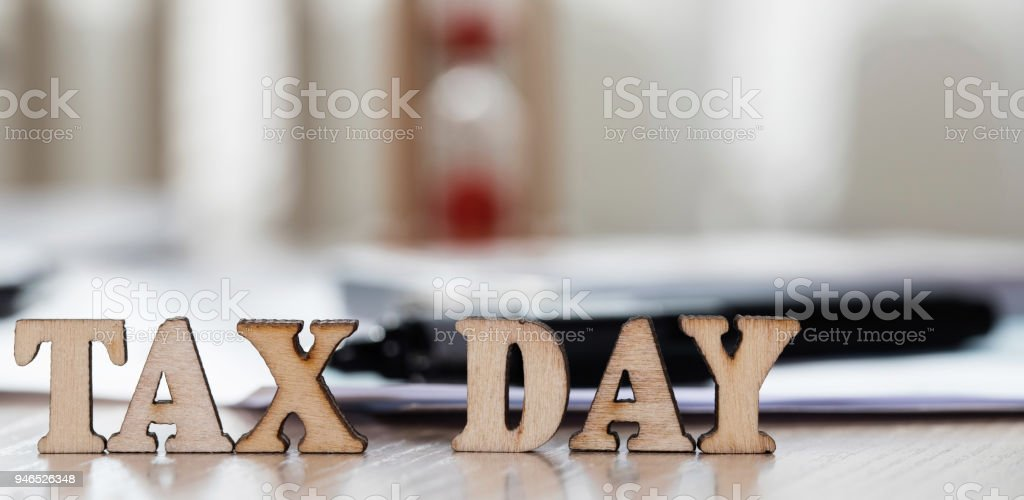 Word Tax Day composed of wooden letters. Money, papers, pen in the background. stock photo