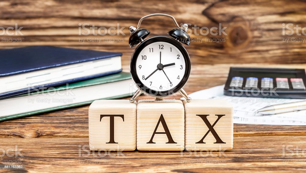 Word 'Tax' with clock on the office workplace. Business concept. stock photo