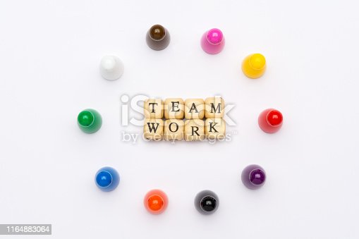 istock Word teamwork on wooden blocks and pawns in various colors on white background, as a concept of success and diversity 1164883064