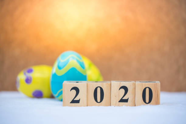 Word text blocks 2020 with colorful easter eggs background. Festive decoration. stock photo