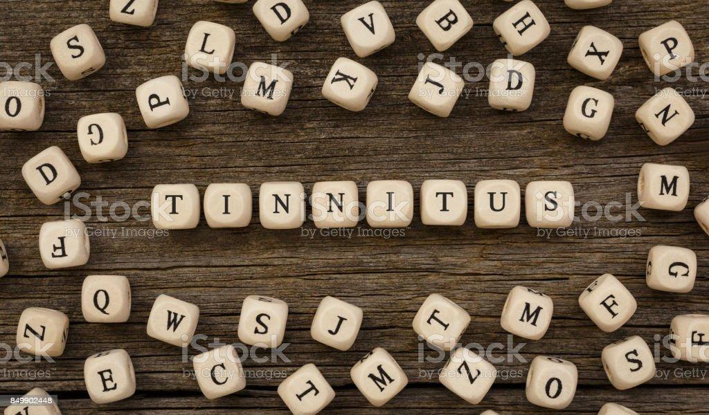 Word TINNITUS written on wood block stock photo