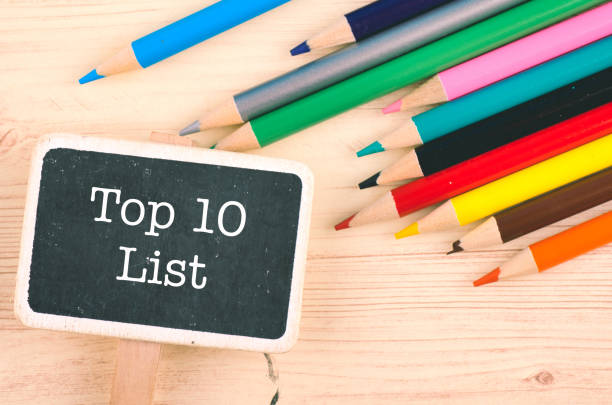 word TOP 10 LIST written on wooden signage over colorful pencil on desk word TOP 10 LIST written on wooden signage over colorful pencil on desk high section stock pictures, royalty-free photos & images