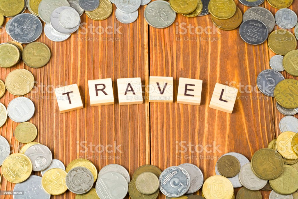 Word TRAVEL on wooden cube with coins frame at wood background. Saving plans for travel budget. stock photo