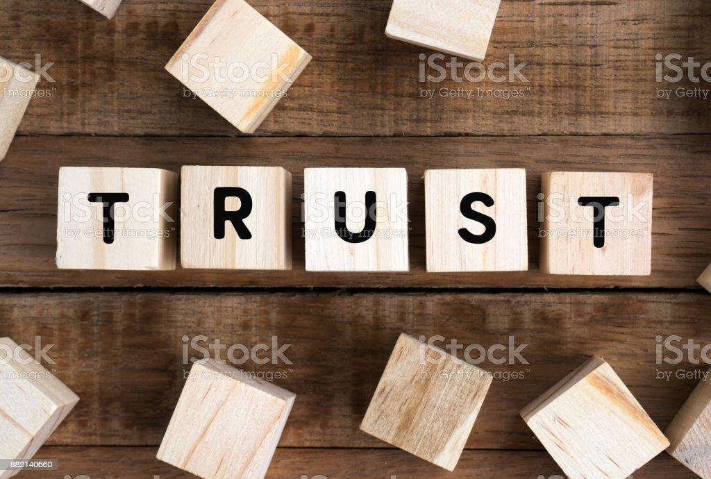 Word trust on a wooden block stock photo