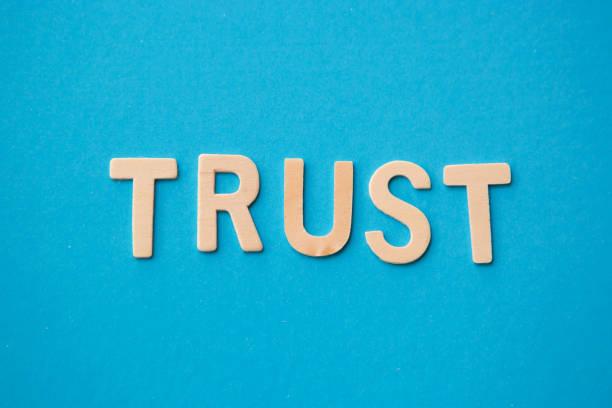 wort vertrauen mit holz alphabet buchstaben auf blauem hintergrund - trust stock-fotos und bilder