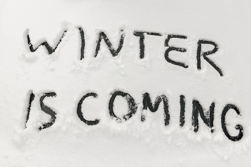 Word winter is coming scraped by hand on the frozen rear glass of car, auto glass covered with snow, cold winter season concept, first snowfall is a difficult weather for drivers and transport