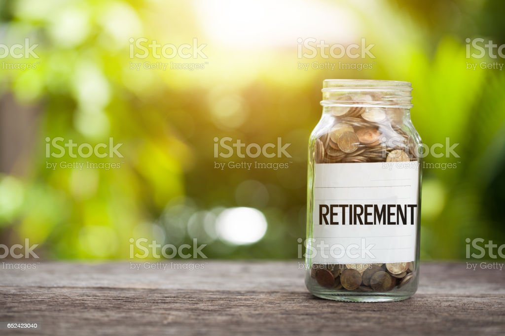 RETIREMENT word with coin in glass jar, Savings and financial investment concept. stock photo