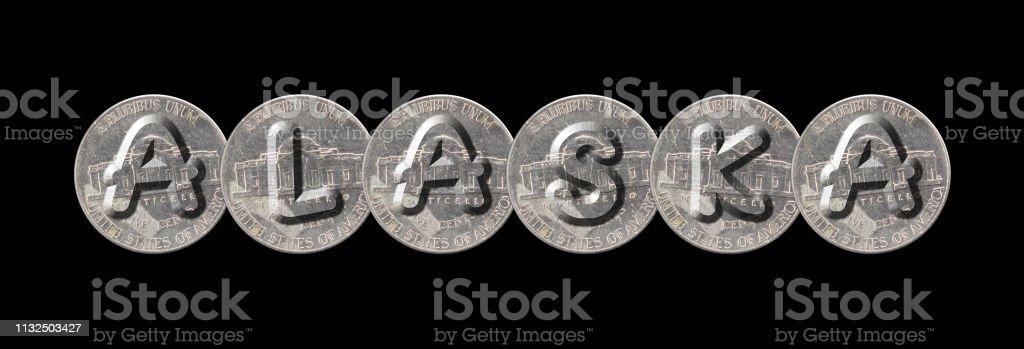 Palavra de ALASKA com cinco moedas dos centavos no fundo preto - foto de acervo