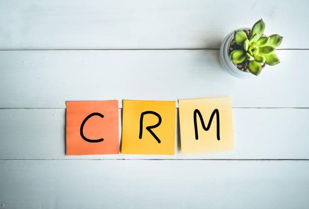 Mot CRM avec note de papier sur fond de table en bois blanc - Photo