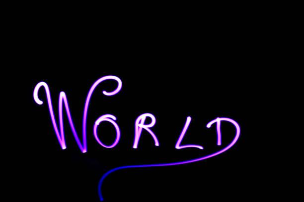 """wort """"welt"""" geschrieben mit einer led-lampe während einer lightpainting-sitzung in der nacht. - handschriftliche typografie stock-fotos und bilder"""