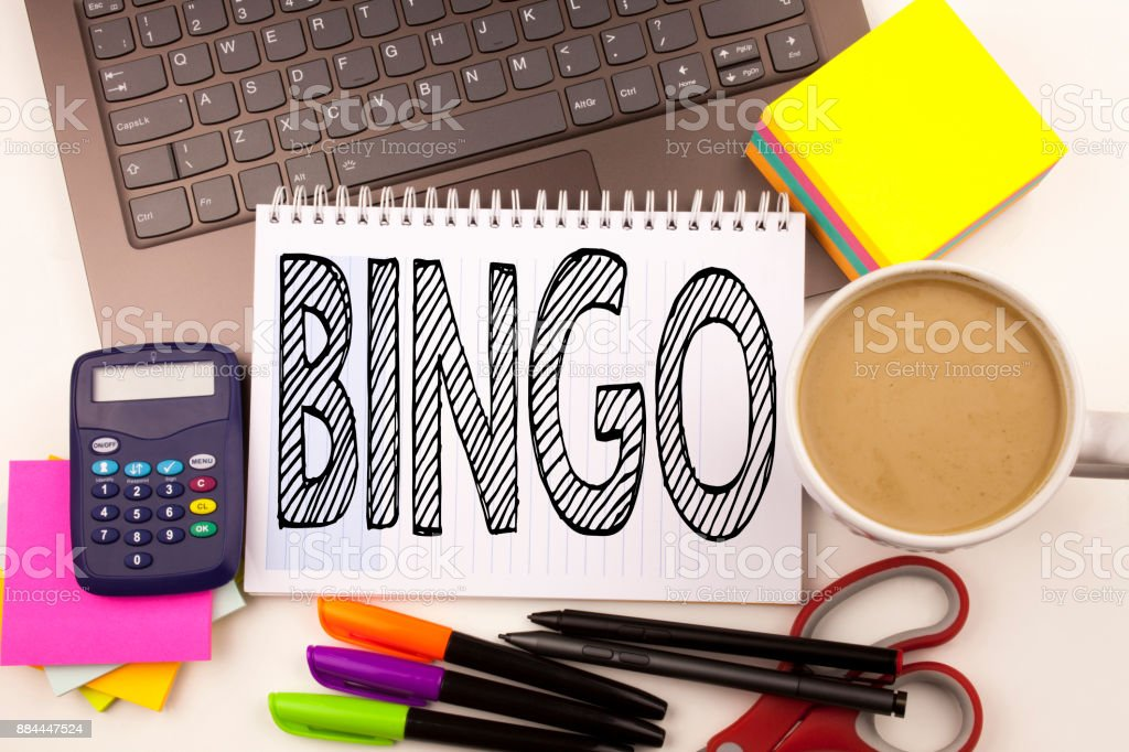 Word writing Bingo in the office with laptop, marker, pen, stationery, coffee. Business concept for Lettering Gambling to Win Price Success Workshop white background with copy space stock photo