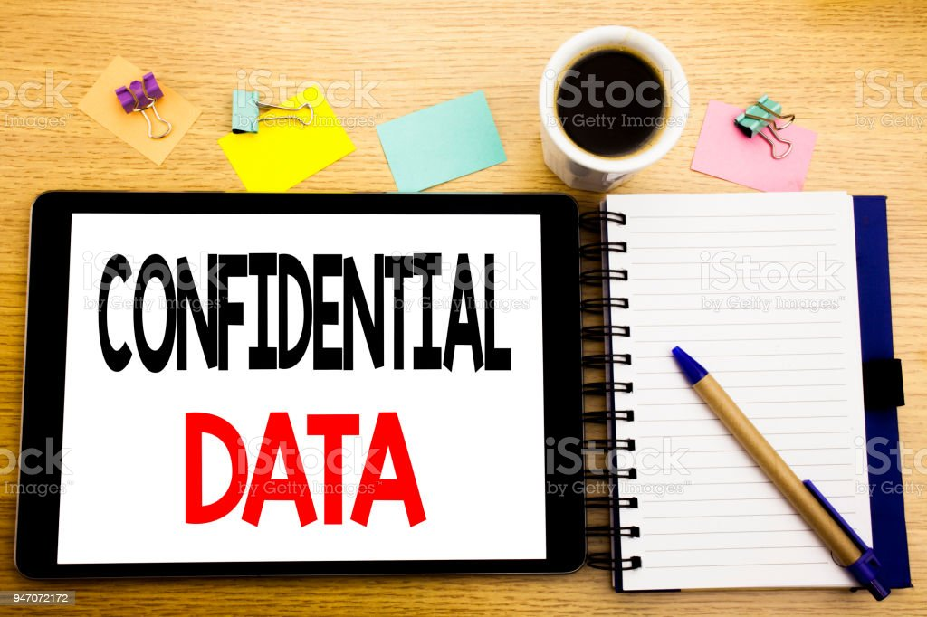 Word, writing Confidential Data. Business concept for Secret Protection Written on tablet laptop, wooden background with sticky note, coffee and pen stock photo