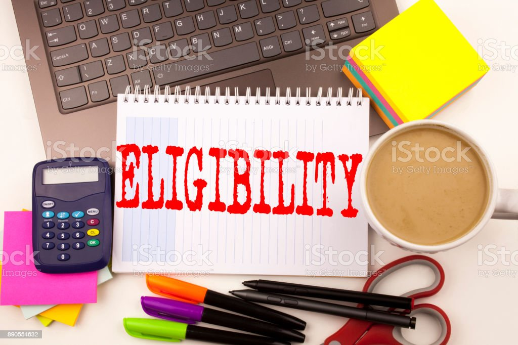 Word writing Eligibility in the office with  laptop, marker, pen, stationery, coffee. Business concept for Suitable Eligible Eligibility Workshop white background with copy space stock photo