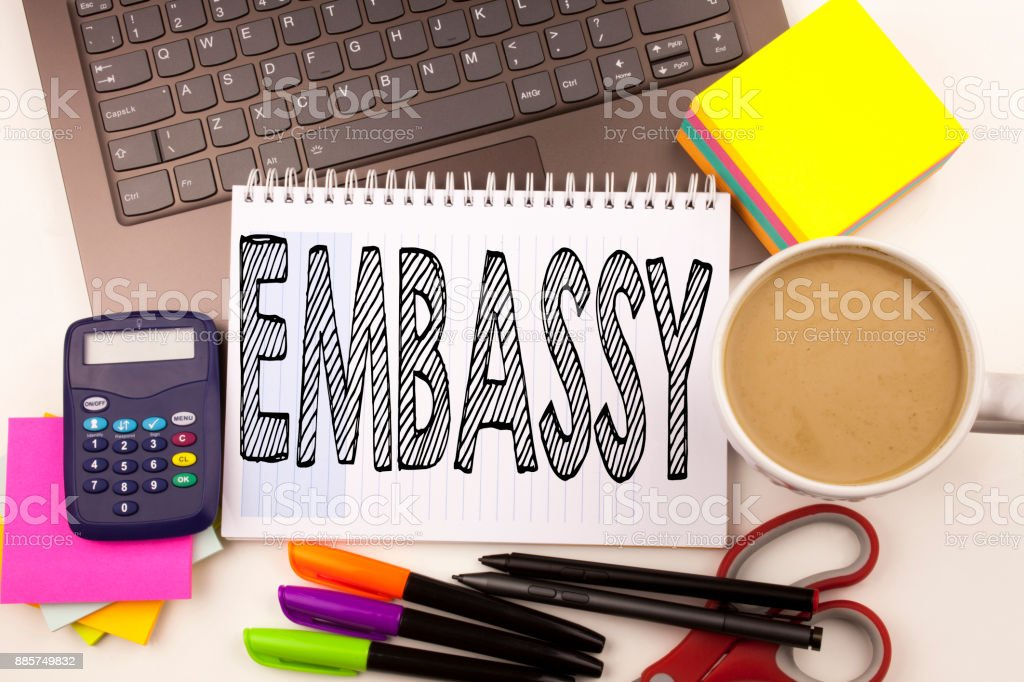 Word writing Embassy in the office with laptop, marker, pen, stationery, coffee. Business concept for Tourist Visa Application Workshop white background with copy space stock photo