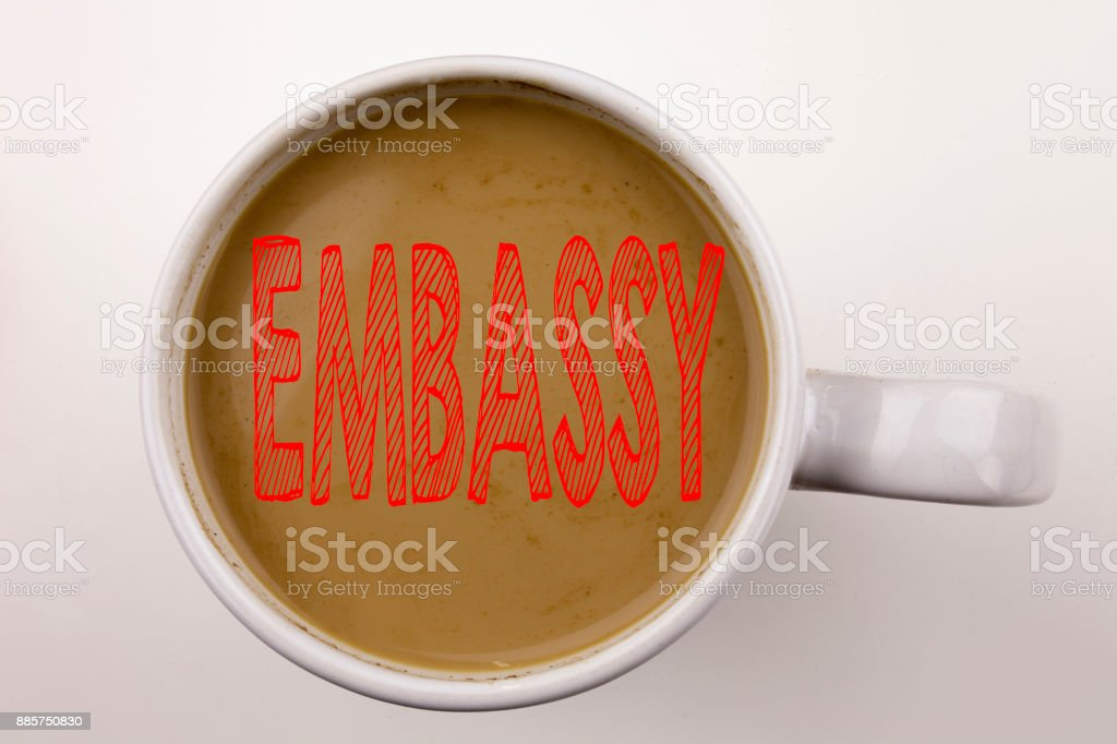 Word, writing Embassy text in coffee in cup. Business concept for Tourist Visa Application on white background with copy space. Black text with red word. stock photo