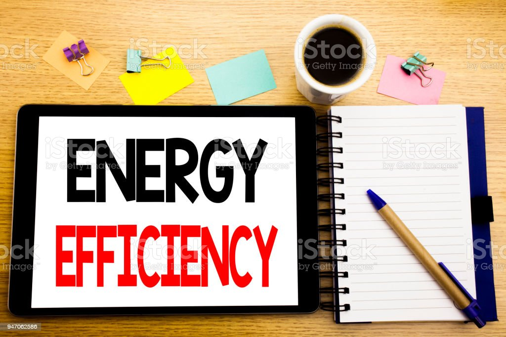 Word, writing Energy Efficiency. Business concept for Electricity Ecology Written on tablet laptop, wooden background with sticky note, coffee and pen stock photo