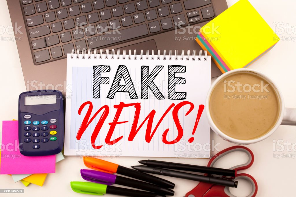 Word writing Fake News in the office with laptop, marker, pen, stationery, coffee. Business concept for Propaganda Newspaper Fake News Workshop white background with copy space stock photo