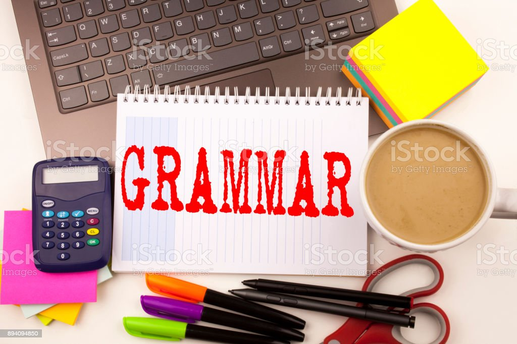 Word writing Grammar in the office with  laptop, marker, pen, stationery, coffee. Business concept for  The Basic Rules of Syntax Grammatical Language Workshop white background with copy space stock photo