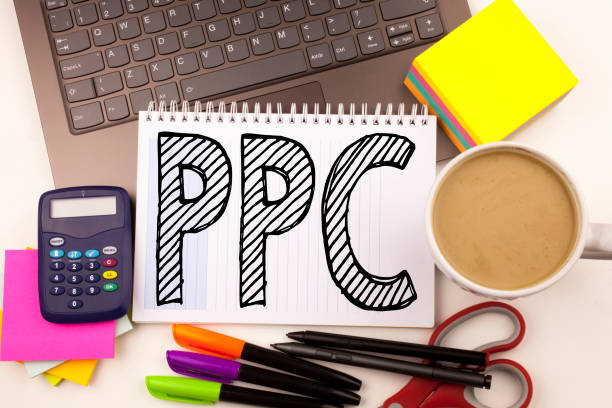 Word writing PPC - Pay per Click in the office with laptop, marker, pen, stationery, coffee. Business concept for Internet SEO Money Workshop white background with copy space – zdjęcie