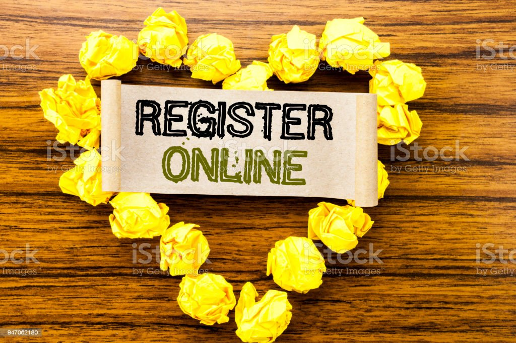 Word, writing Register Online. Business concept for Internet Subscribe written on sticky note paper on the dark wooden background. With yellow folded paper heart meaning love or adoration. stock photo