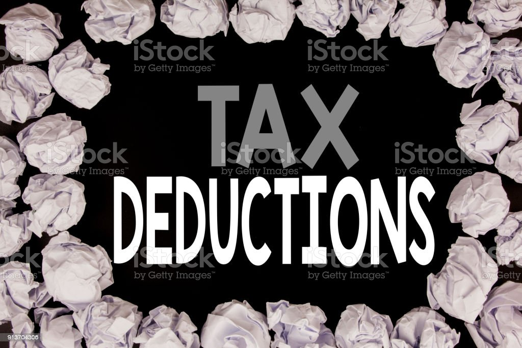 Word, writing Tax Deductions. Business concept for Finance Incoming Tax Money Deduction written on black background with copy space on old background with folded paper balls stock photo