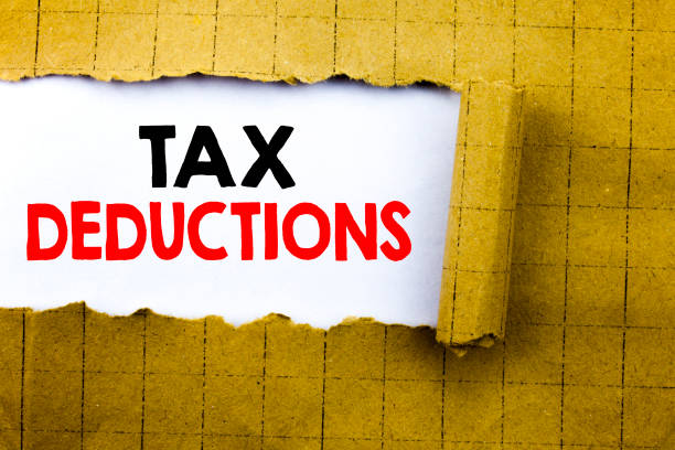 Word, writing Tax Deductions. Business concept for Finance Incoming Tax Money Deduction written on white paper on the yellow folded paper. stock photo
