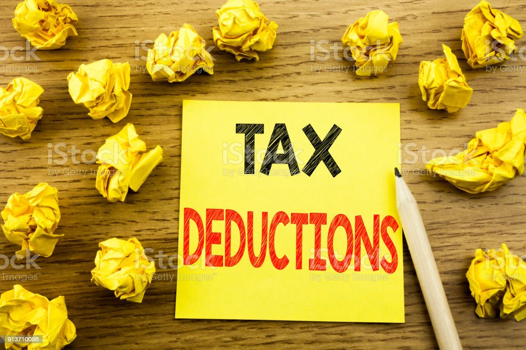 Word, writing Tax Deductions. Business concept for Finance Incoming Tax Money Deduction written on sticky note paper on the wooden background. Folded yellow papers on the background stock photo