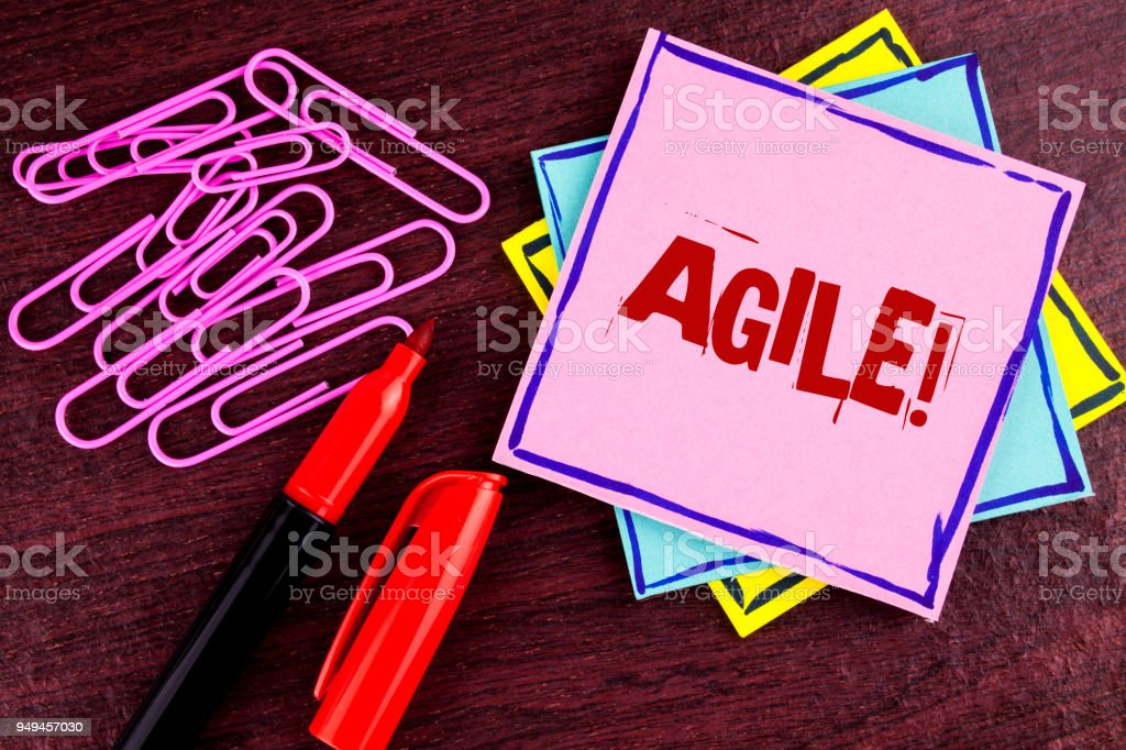 Word writing text Agile Motivational Call. Business concept for Develop an agility towards technological chnage written on Pink Sticky Note Paper on wooden background Marker and Paper Clips stock photo