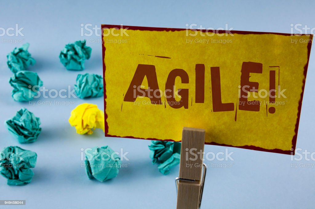 Word writing text Agile Motivational Call. Business concept for Develop an agility towards technological chnage written on Yellow Sticky Note Paper in Clip on the plain background Paper Balls stock photo