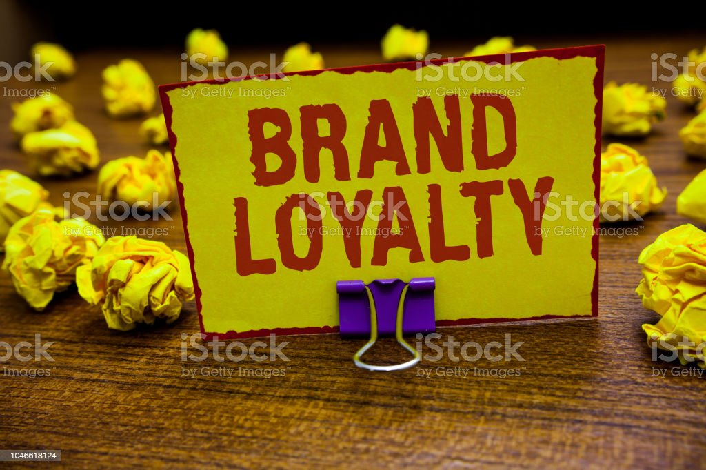 Word writing text Brand Loyalty. Business concept for Repeat Purchase Ambassador Patronage Favorite Trusted Clip holding yellow paper note crumpled papers several tries mistakes. stock photo