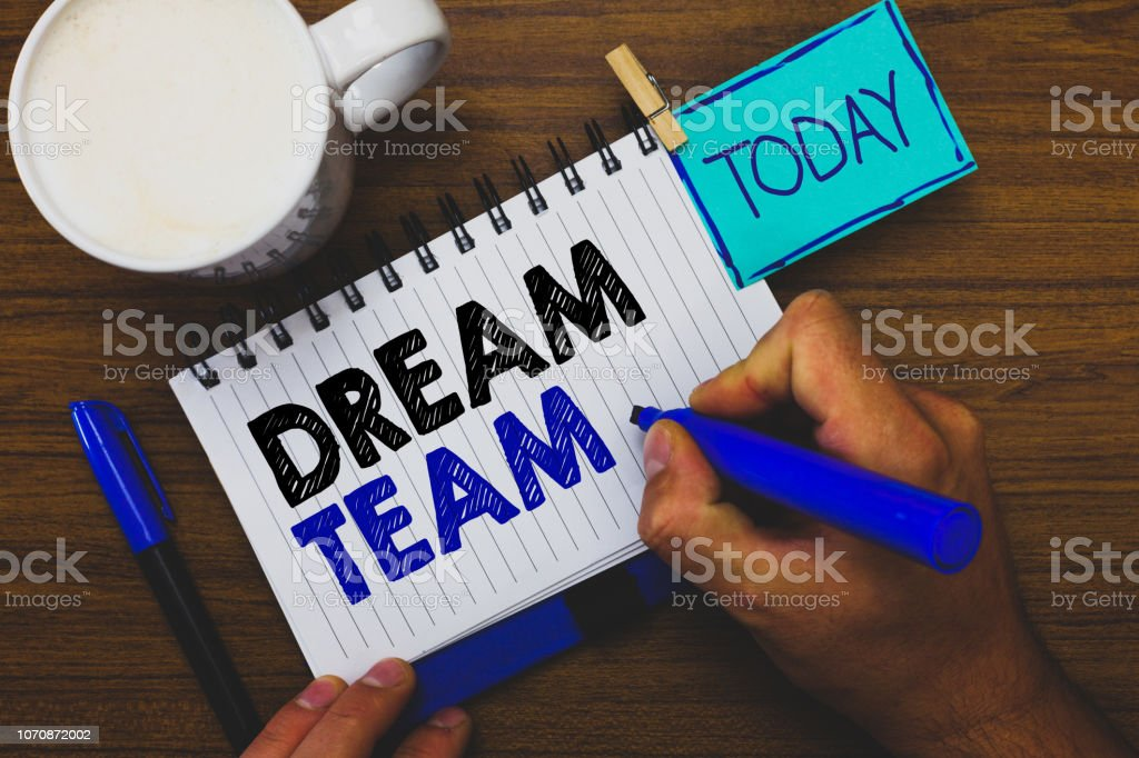 Word writing text Dream Team. Business concept for Prefered unit or group that make the best out of a person Man holding marker notebook clothespin reminder wooden table cup coffee. stock photo