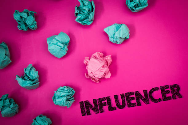 Word writing text Influencer. Business concept for Person who influences and affect decisions opinions of others Ideas messages thoughts pink background crumpled papers several tries. stock photo
