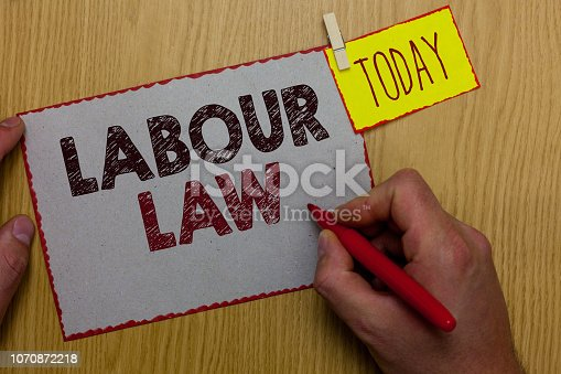 istock Word writing text Labour Law. Business concept for Rules implemented by the state between employers and employee Man holding marker paper clothespin reminder express ideas wooden table. 1070872218