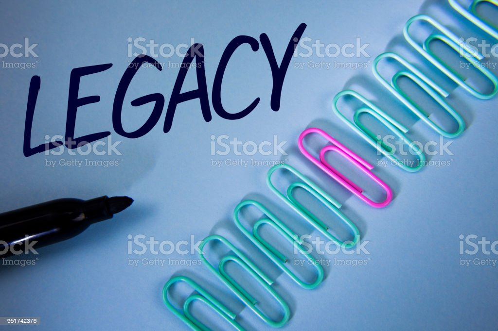 Word writing text Legacy. Business concept for Transmitted Received from an ancestor Money Properties given by will written on Plain Blue background Paper Clips and Marker next to it. stock photo