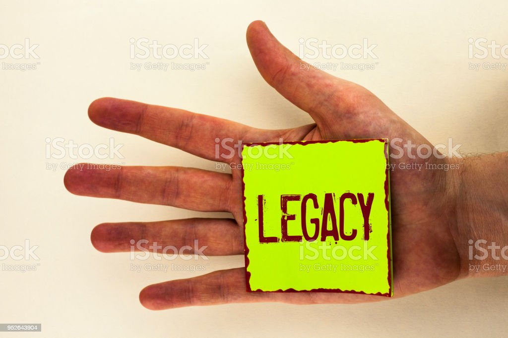 Word writing text Legacy. Business concept for Transmitted Received from an ancestor Money Properties given by will written on Sticky Note Paper placed on the Hand on the plain background. stock photo