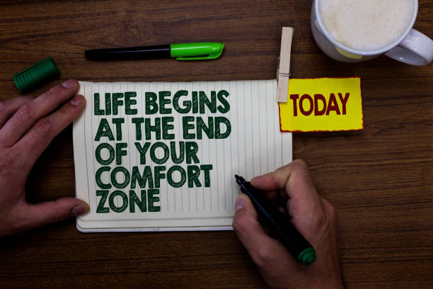 Word writing text Life Begins At The End Of Your Comfort Zone. Business concept for Make changes evolve grow Man holding marker notebook clothespin reminder wooden table cup coffee. stock photo