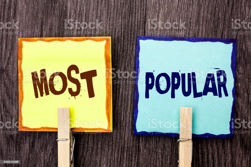 Word writing text Most Popular. Business concept for Top Rating Bestseller Favorite Product or Artist 1st in ranking written on Sticky Note Papers Holding with Wooden Clip on the wooden background. stock photo