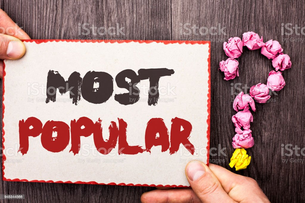 Word writing text Most Popular. Business concept for Top Rating Bestseller Favorite Product or Artist 1st in ranking written on Cardboard Piece Holding By Hand on wooden background Question Mark. stock photo