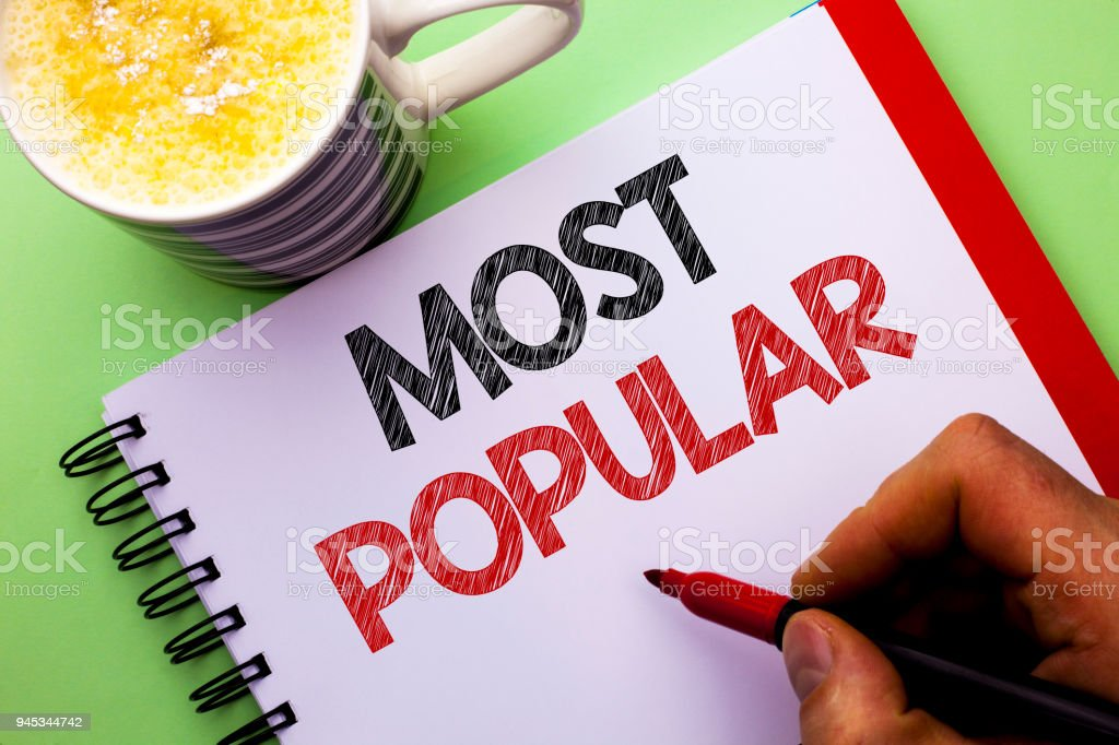 Word writing text Most Popular. Business concept for Top Rating Bestseller Favorite Product or Artist 1st in ranking written by Man on Notebook Book Holding Marker on the plain background Coffee Cup stock photo