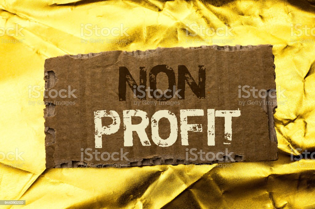 Word writing text Non Profit. Business concept for Charitable Wrothless Philanthropy Aid Unlucrative Profitless written on tear Cardboard Piece on the Golden textured background. stock photo